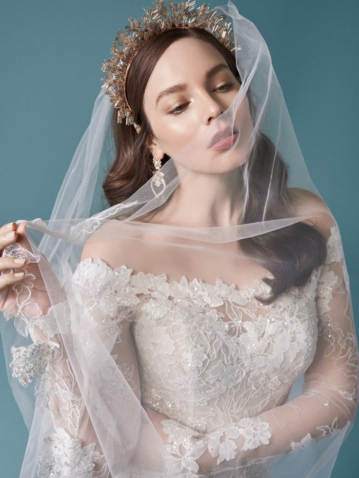 Model Wearing Off-the-Shoulder Sleeve Wedding Dress with Cathedral Wedding Veil Called Emiliano by Maggie Sottero