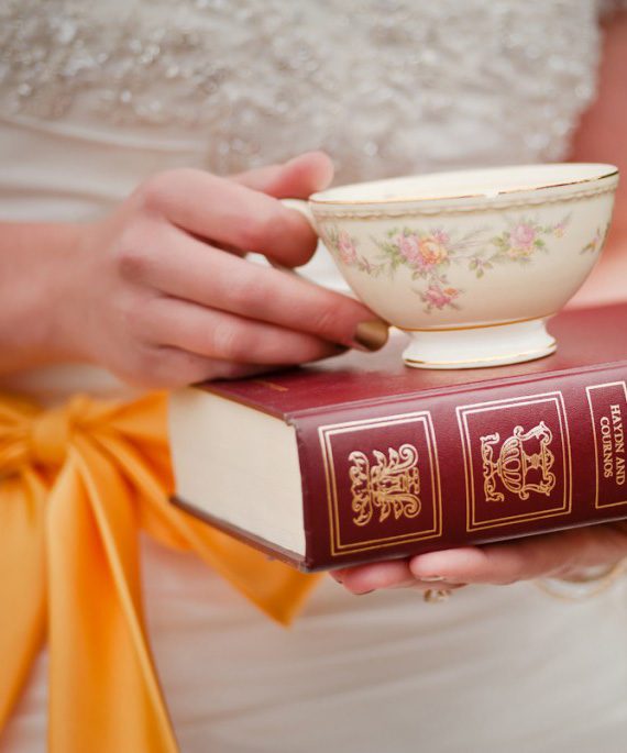 Bride Holding Teacup and Book in Wedding Photo Shoot