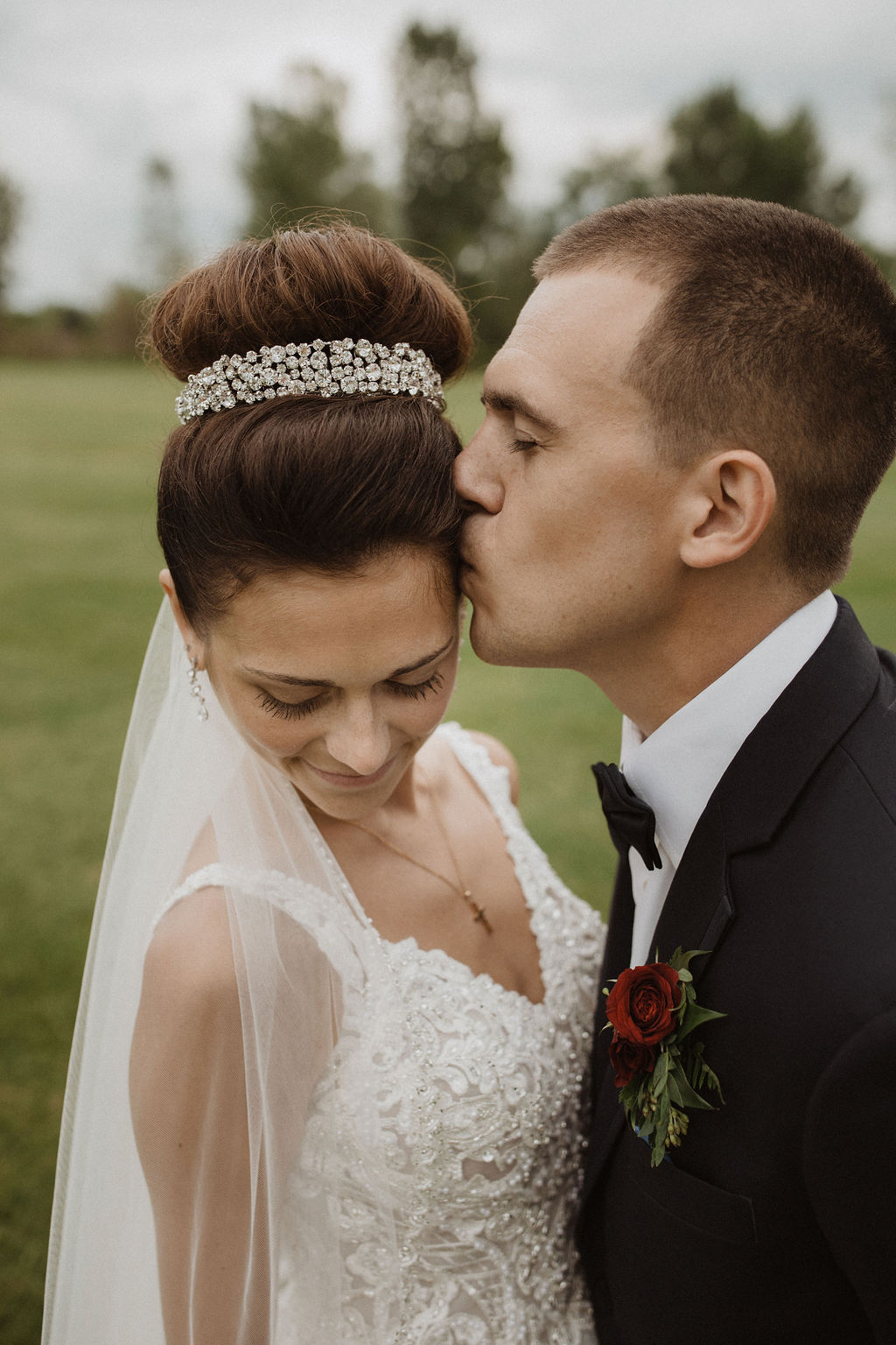 Groom Kissing Real Bride Wearing Crown and Princess Wedding Dress Called Taylor Lynette by Maggie Sottero