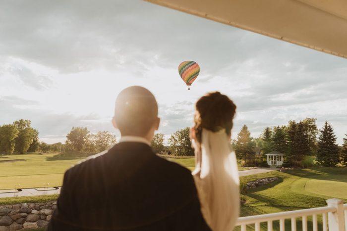 Bride and Groom Looking at Hot Air Balloon at Real Wedding
