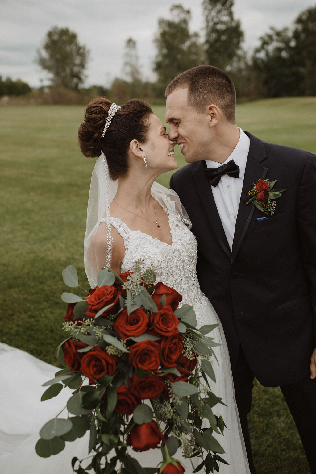 Groom Holding Real Bride While She Holds a Red Rose Bouquet