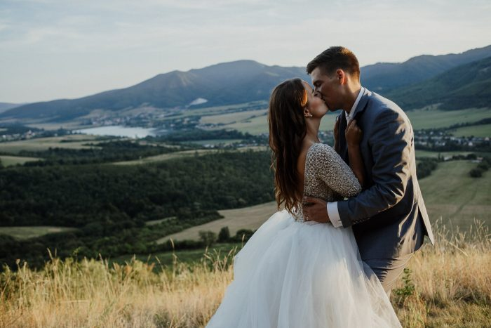 Groom Kissing Real Bride Wearing Ball Gown Wedding Dress by Maggie Sottero in Slovakia