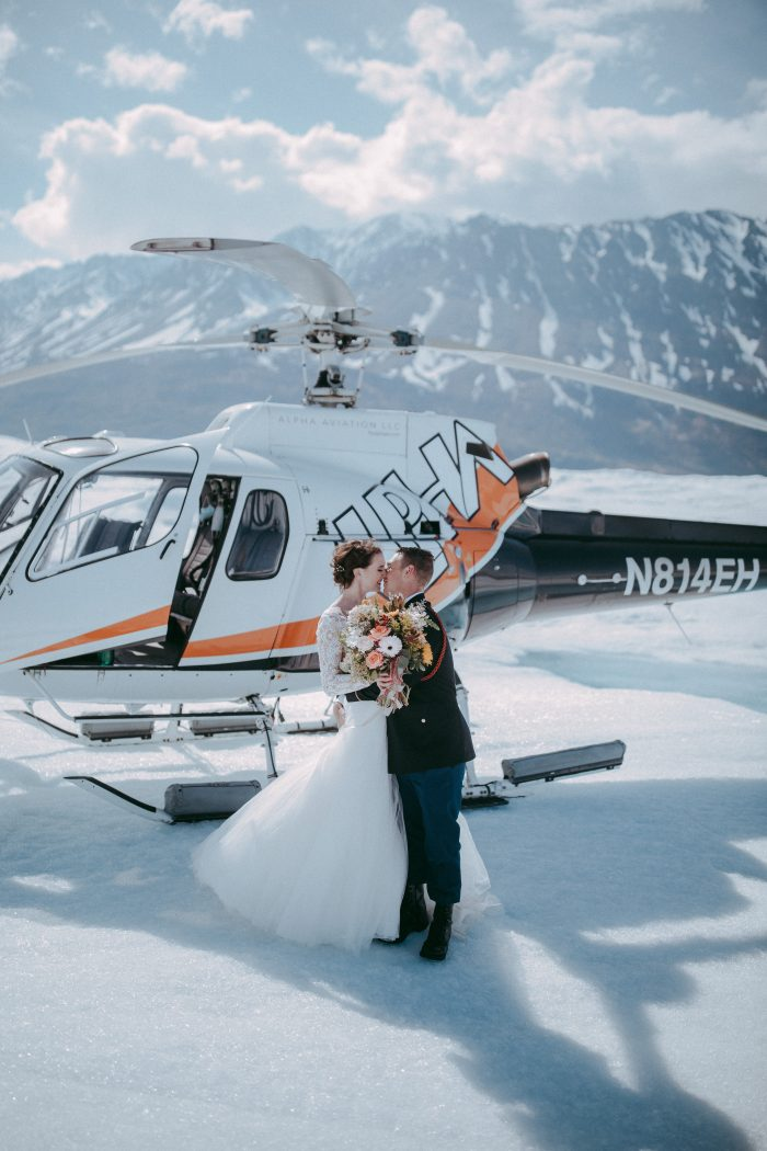 Groom with Real Bride Getting Married on Glacier in Alaska in Romantic Destination Wedding with Helicopter Behind Them