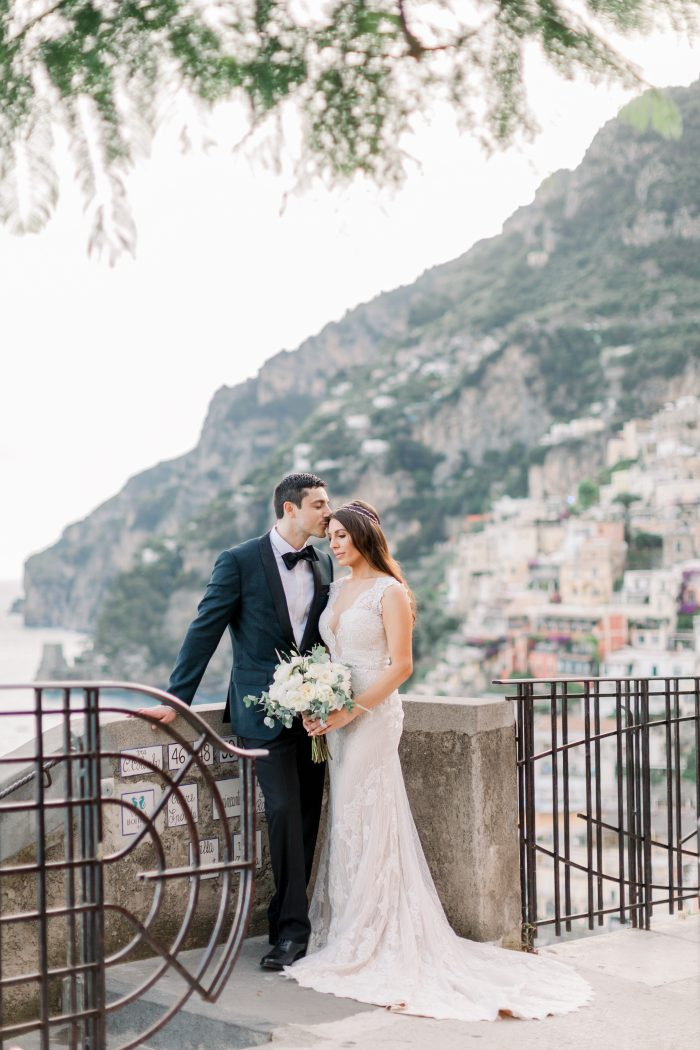 Groom Kissing Bride Wearing Lace Sheath Wedding Dress by Maggie Sottero in Positano Italy