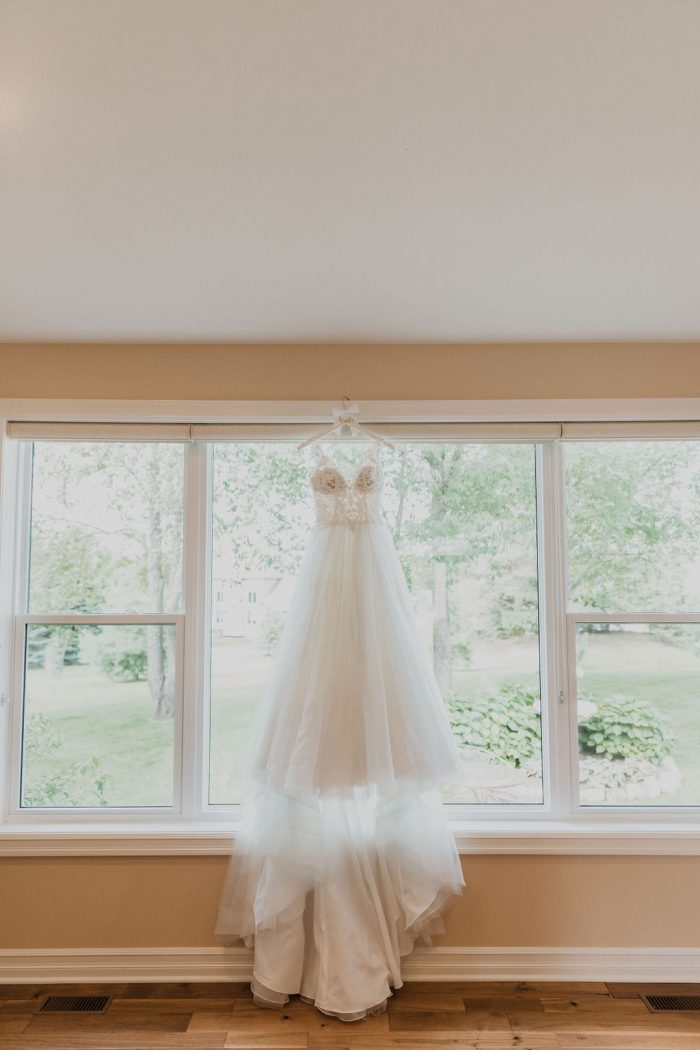 Sparkly Ball Gown Wedding Dress Called Taylor by Maggie Sottero Hanging from Window