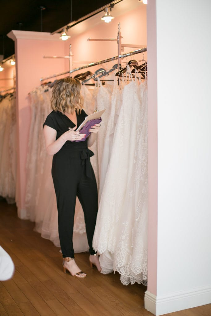 Bridal Stylist Browsing Row of Wedding Dresses at a Local Boutique