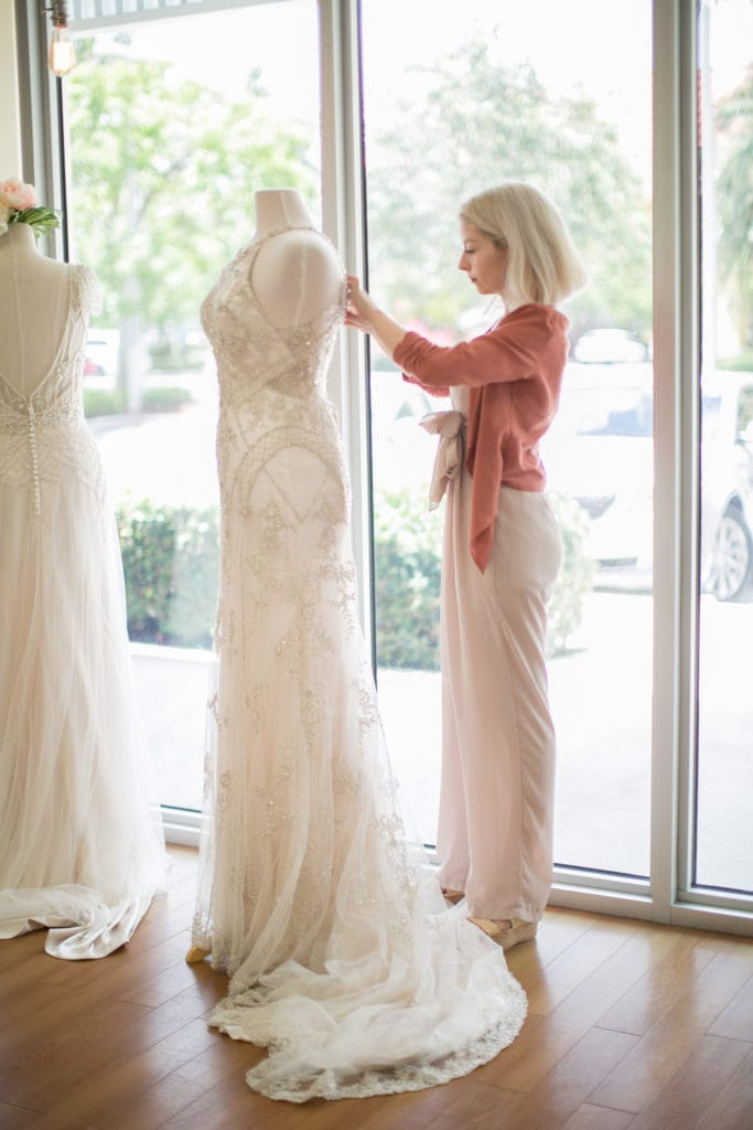 Bridal Stylist Putting a Maggie Sottero Wedding Dress on a Mannequin at a Store Event
