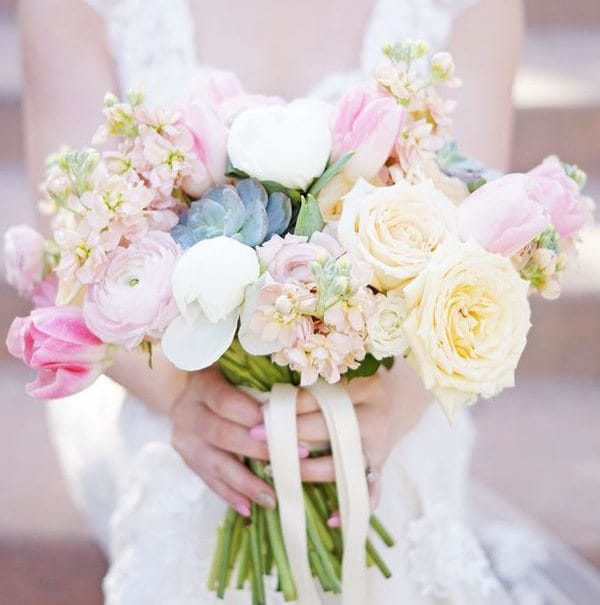 A photo of a bride holding a bouquet of flowers.