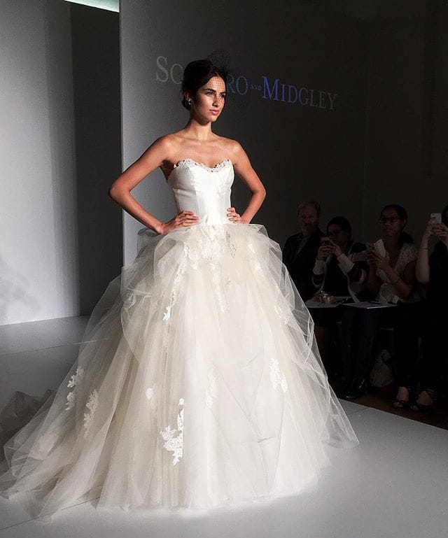 Model Walking Down a Runway Wearing Ball Gown Wedding Dress by Rebecca Ingram