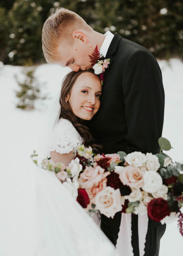 Groom Kissing Bride Wearing a Romantic Winter Wedding Makeup Look and Maggie Sottero Modest Wedding Gown