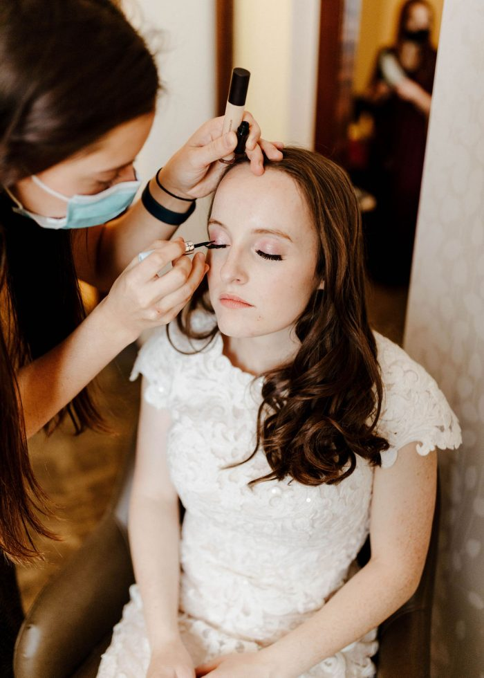 Makeup Artist Putting on Bride's Romantic Winter Wedding Makeup While Bride Wears Maggie Sottero Wedding Dress