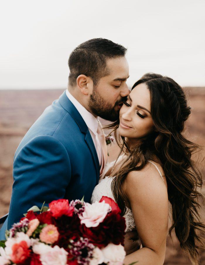 Groom in Moab Kissing Bride Wearing Rebecca Ingram Wedding Dress and Romantic Bridal Makeup