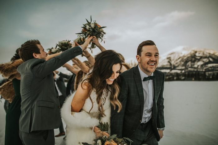 Bride Wearing Halter Neck Wedding Dress by Sottero and Midgley Walking with Groom in the Snowy Mountains Walking Through Arch Made by Wedding Party