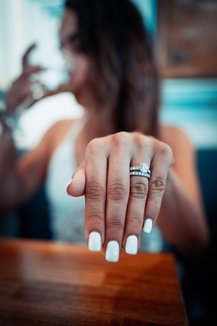 Woman with White Painted Nails HOlding out Hand with Engagement Ring and Wedding Band on Her Finger