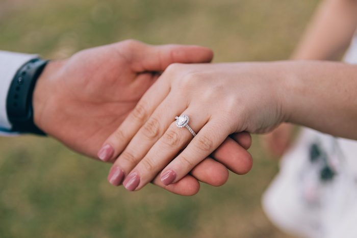 Engaged Couple's Hands with Simple Diamond Engagement Ring