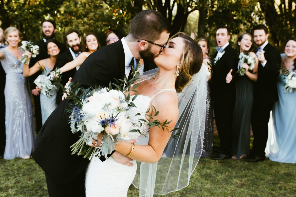 Groom Kissing Real Bride Wearing Maggie Sottero Wedding Dress While Guests Cheer in Background