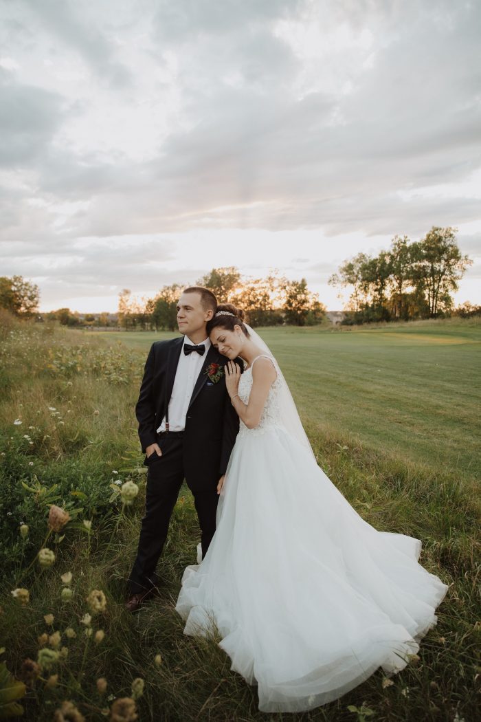 Bride Wearing Ball Gown Wedding Dress Called Taylor Lynette by Maggie Sottero While Resting Her Head on Groom's Shoulder