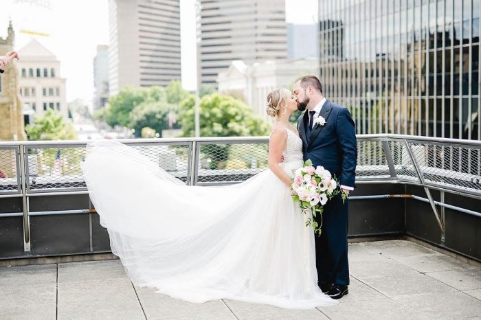 Groom Kissing Real Bride with City Backdrop While Bride's Maggie Sottero Wedding Dress Flows Behind Her