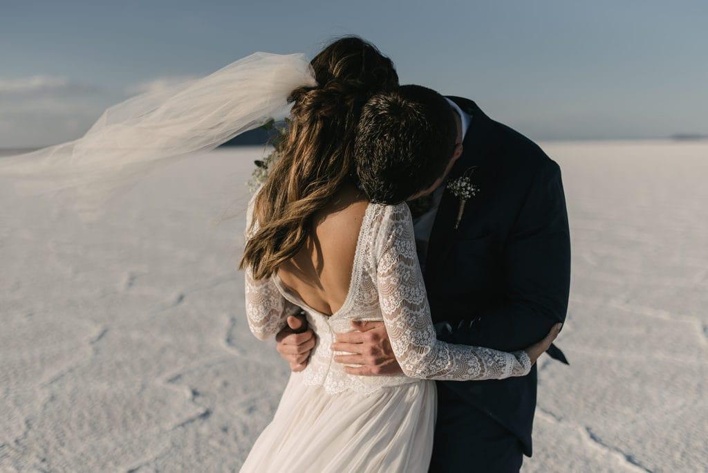 Groom Hugging Bride as Her Wedding Veil Flows Back in the Wind