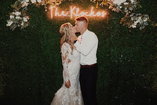 Groom Under Pink Neon Sign Kissing Real Bride Wearing Dakota Wedding Gown by Sottero and Midgley