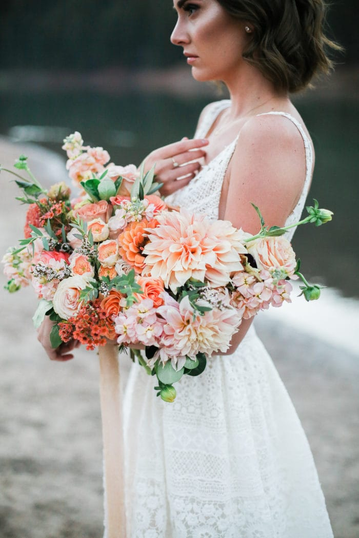 Bride on the beach holding a colorful wedding bouquet