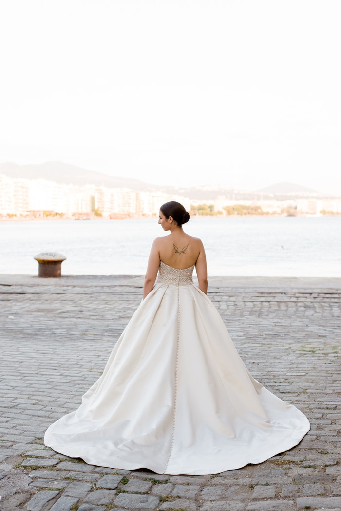 Real Bride Wearing Slicked Back Hair and Strapless Ball Gown Wedding Dress Called Phoenix by Sottero and Midgley