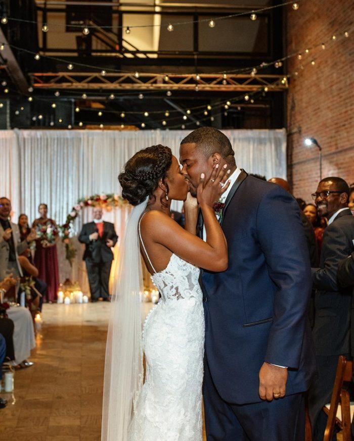 Groom Hugging Bride Wearing Wedding Day Hairstyle with Braid and Ballerina Bun