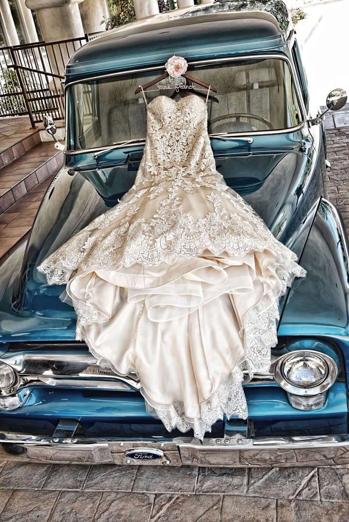 Elegant Celebration with Lace Wedding Gown, Classic Cars, and Flirty Details. Jennita wedding dress by Maggie Sottero.