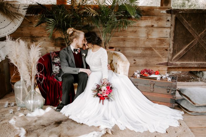 Groom Sitting with Bride on a Couch While Bride is Wearing Modest Boho Wedding Dress Called Deirdre by Maggie Sottero