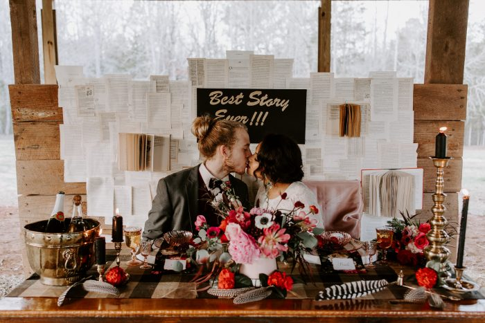 Bride and Groom Kissing Behind Table Decorated with Red Dining Ware and Red Cake for Valentine's Day