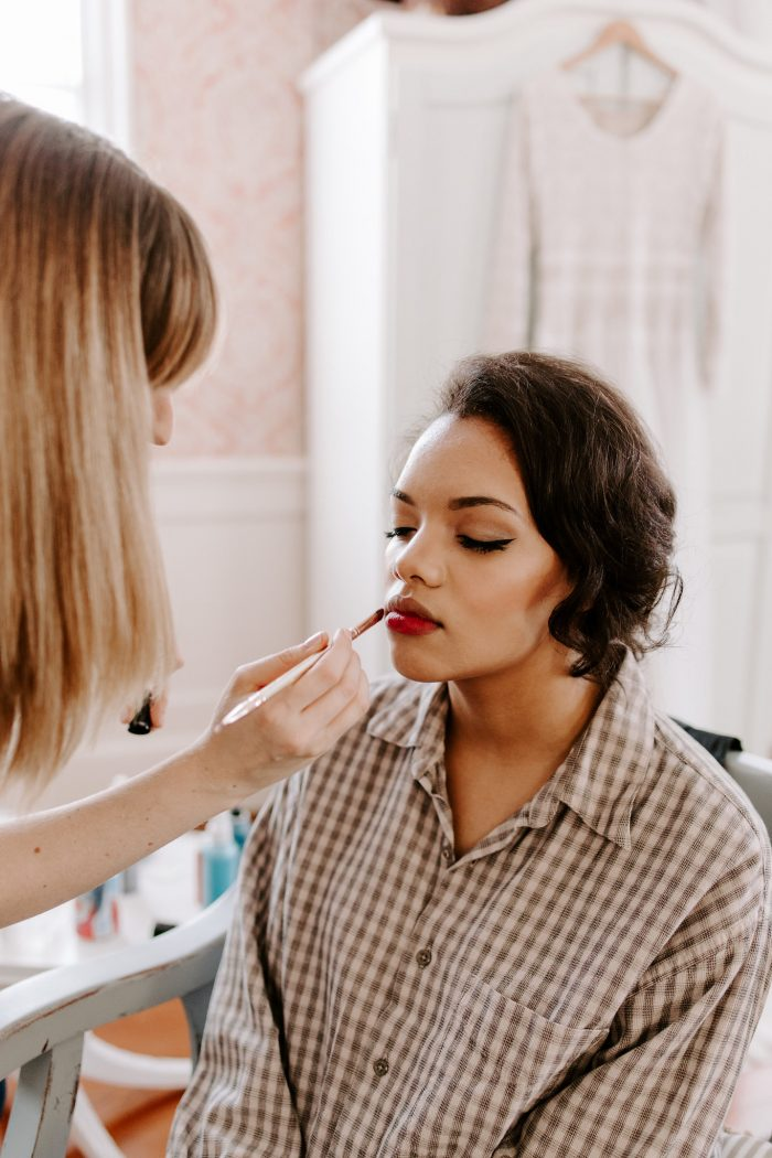 Makeup Stylist Putting on Bride's Red Lipstick