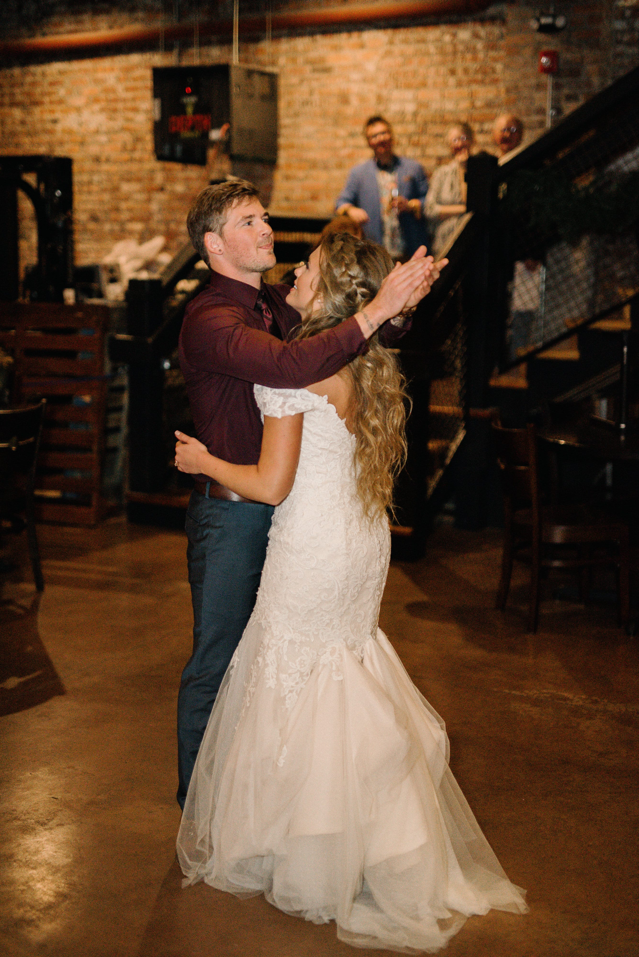 Adventure-loving couple planned winter wedding in brewery! Maggie Bride Destiny wearing Afton by Maggie Sottero.