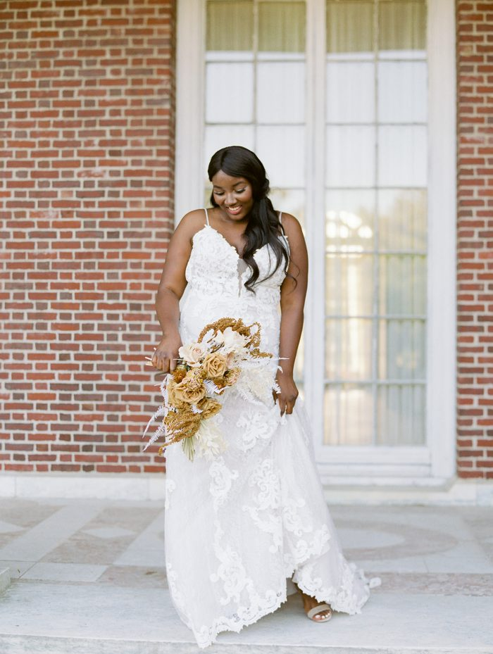 Black Bride Wearing Lace A-line Wedding Dress Called Tuscany Lane by Maggie Sottero and Holding Autumn Wedding Bouquet