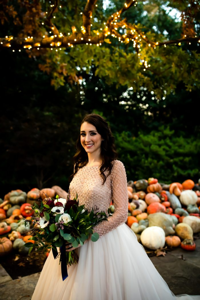 Real Bride Wearing Vintage Ball Gown Wedding Dress and Standing in Front of Pumpkins