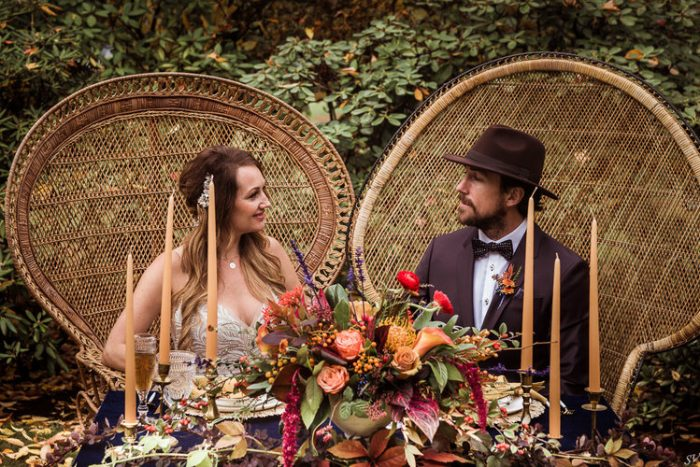 Bride and Groom Kissing at Outdoor Table Setting Featuring Caramel and Apricot Tones for Fall