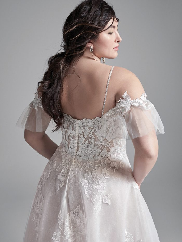 Curvy Model Wearing Plus Size Cold Shoulder A-line Wedding Dress Called Houston by Sottero and Midgley