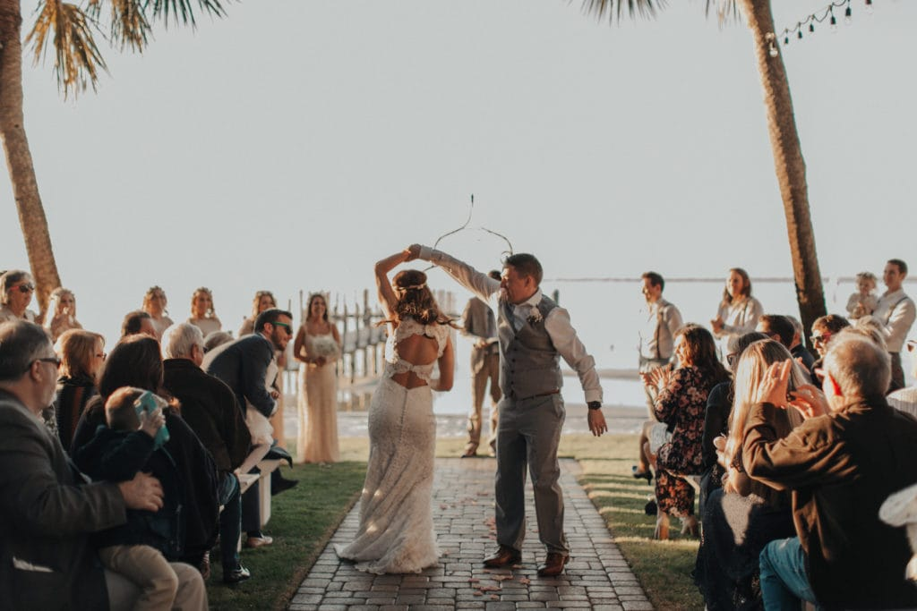 Groom Spinning Bride Wearing Boho Wedding Dress While Walking Down the Aisle After Wedding Ceremony
