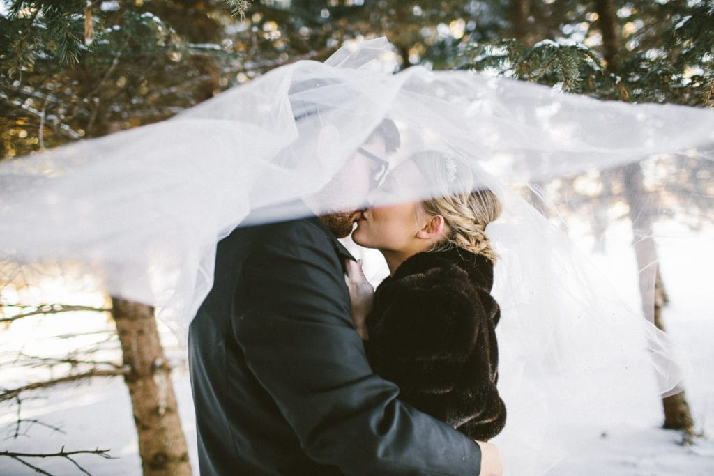 Groom in Snow Kissing Real Bride Wearing Vintage Ball Gown Wedding Dress Called Allen by Sottero and Midgley