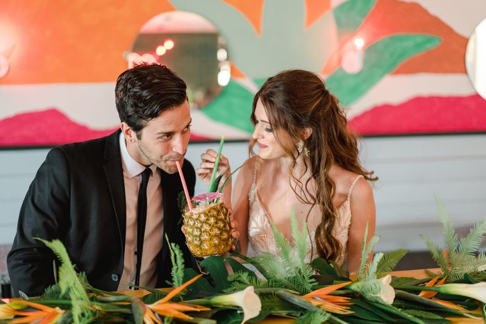 A photo of a bride and groom drinking out of a pineapple at a tropical style wedding.