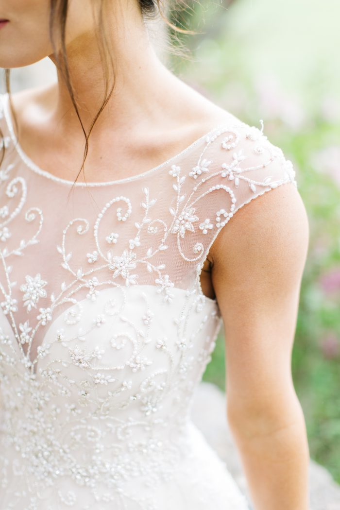 A close-up photo of a bride wearing a romantic style wedding dress.
