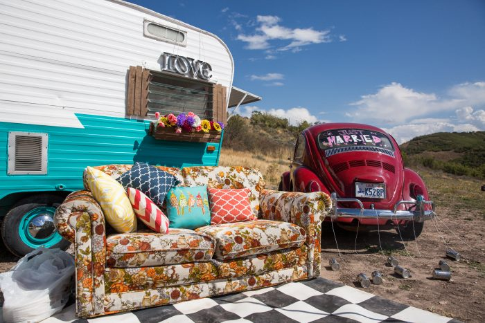 Couch in front of trailer and a red car in the mountains