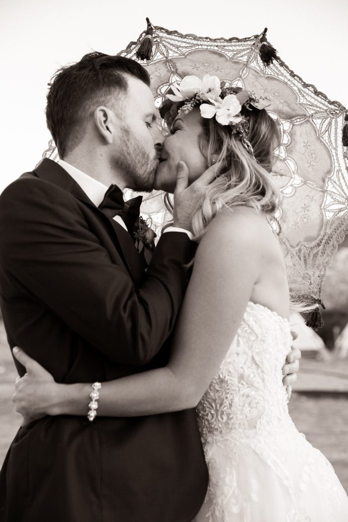 Bride wearing Watson by Sottero and Midgley with a Parasol kissing her groom