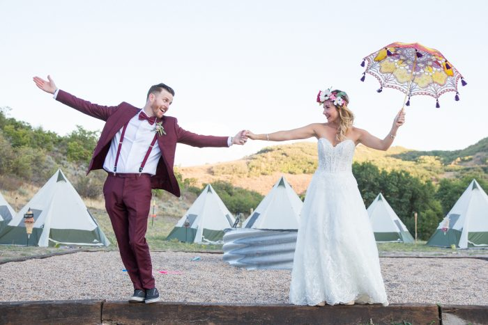 Bride wearing Watson lace dress by Sottero and Midgley and Groom with tents and a colorful parasol