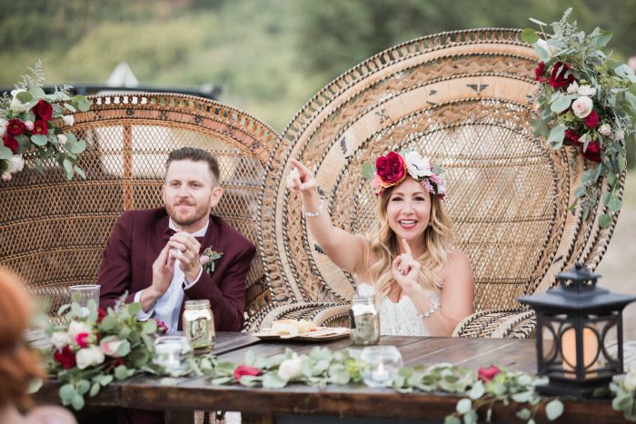 Bride and Groom in wicker chairs surrounded by red and white flowers and greenery
