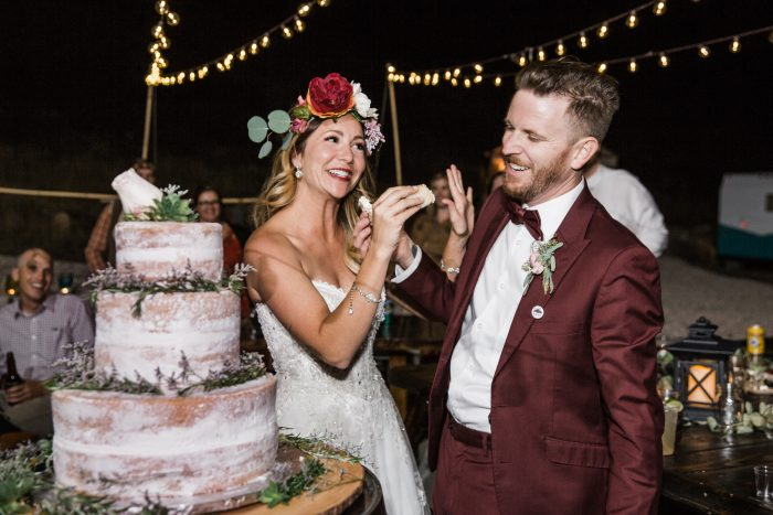 Bride wearing Watson by Maggie Sottero and Groom eating a rustic inspired cake at night