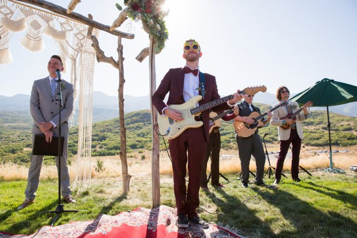 Groom with a guitar at an outdoor wedding
