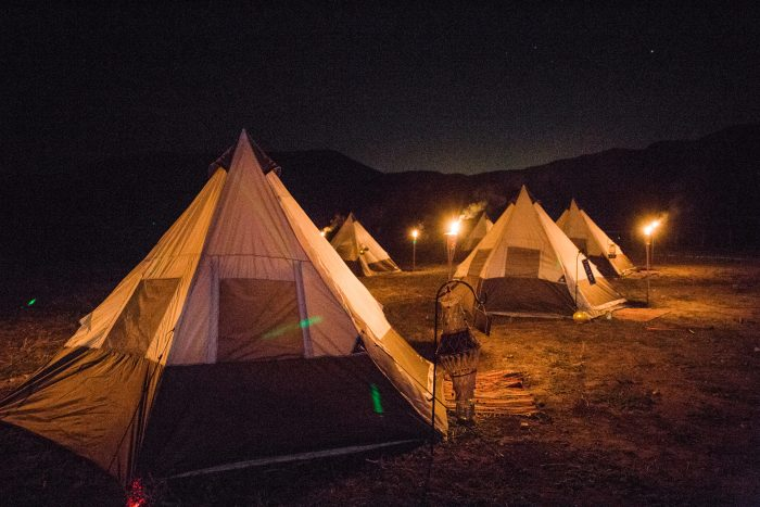 Teepees lit up at night