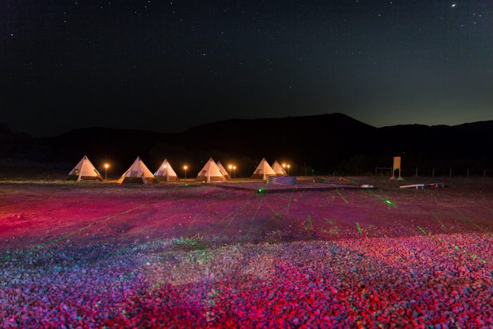 Tents lit up in a colorful field