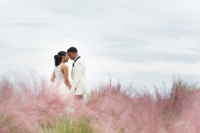 Bride wearing Lisette by Maggie Sottero and Groom in a grass field