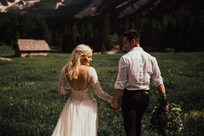 Couple walking through a field in the mountains